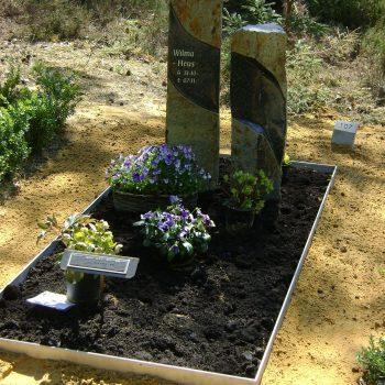 Twee zuilen van Turks Basalt als grafsteen. Tuintje met paarse violen.