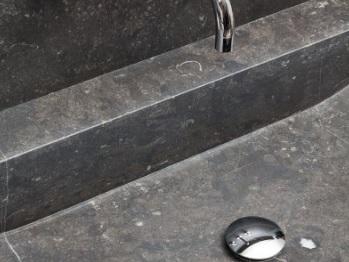 stukje van een wastafel met zilverkleurige kraan en spoelstop