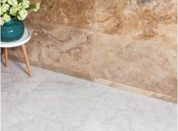 vloer en muur van natuursteen met links een klein houten krukje met daarop een plant.