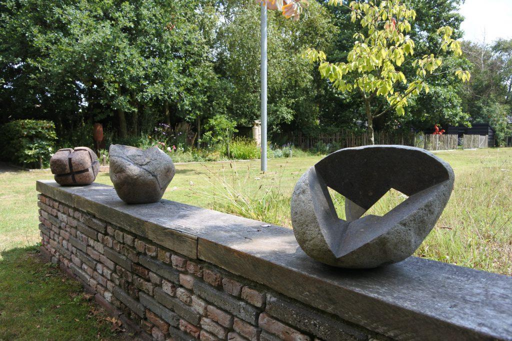 drie kunstwerken van steen op een muurtje gelegen