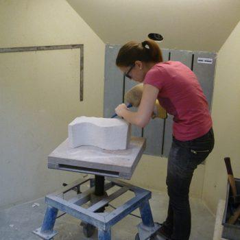 een dame is aan het beeldhouwen als bedrijfsuitje